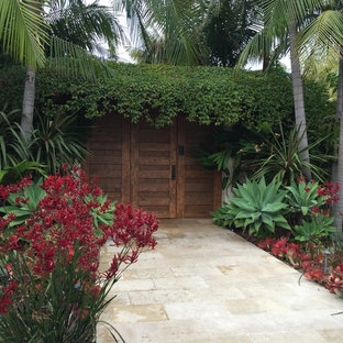 This is an example of a mid-sized tropical full sun front yard stone garden path in Los Angeles.