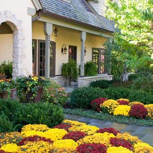 Photo of a traditional front yard stone flower bed in Chicago.