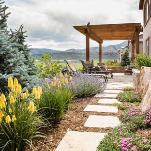 Medium sized classic back xeriscape full sun garden for summer in Denver with natural stone paving.