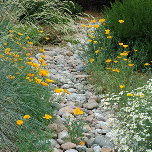 Design ideas for a large mediterranean partial sun backyard stone landscaping in Denver.