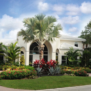This is an example of a mid-sized tropical full sun front yard concrete paver landscaping in Miami for summer.