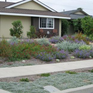 Создайте стильный интерьер: солнечный участок и сад среднего размера на переднем дворе в средиземноморском стиле с подъездной дорогой, освещенностью и мощением тротуарной плиткой - последний тренд
