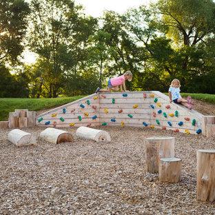 Immagine di un piccolo giardino con uno spazio giochi, un pendio, una collina o una riva e pacciame