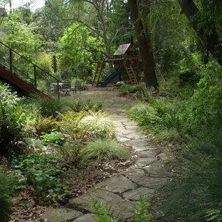 Diseño de jardín rústico, de tamaño medio, en patio trasero, con exposición reducida al sol, adoquines de piedra natural y parque infantil