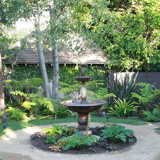 Réalisation d'un jardin arrière méditerranéen avec un point d'eau et une exposition ombragée.