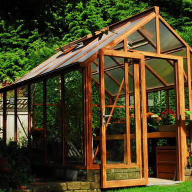 Cedar-Look Aluminum Greenhouse - Believe it or not, this is an aluminum greenhouse!  Our unique powder coat finish gives the appearance of beautiful cedar but without the yearly maintenance.  This greenhouse comes with 6mm full piece glass, commercial storefront door, decorative beauty capping and a lifetime warranty!