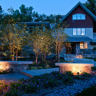 Photo of a large contemporary front yard stone retaining wall landscape in Milwaukee.