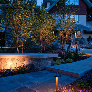 This is an example of a large craftsman front yard stone landscaping in Milwaukee.