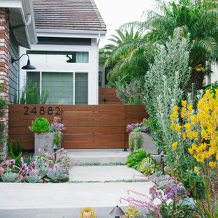 Inspiration for a mid-sized contemporary drought-tolerant and partial sun front yard concrete paver and wood fence garden path in Orange County.