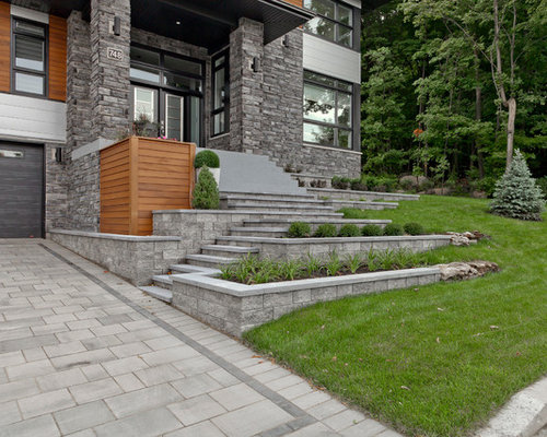 Photo Of A Contemporary Front Yard Retaining Wall Landscape In Montreal.