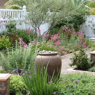Cette image montre un jardin arrière style shabby chic de taille moyenne avec une entrée ou une allée de jardin, du gravier et une exposition ensoleillée.