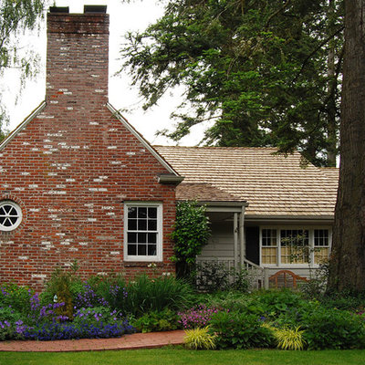 Inspiration for a traditional front yard brick flower bed in Portland.
