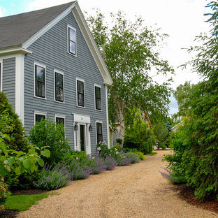 Photo of a mid-sized farmhouse partial sun front yard gravel driveway in Boston.