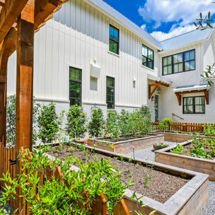 Photo of a mid-sized farmhouse full sun side yard gravel and wood fence raised garden bed in New Orleans.
