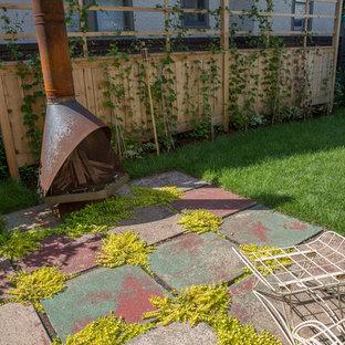 Moderner Garten im Frühling, hinter dem Haus mit direkter Sonneneinstrahlung, Betonplatten und Kamin in Minneapolis