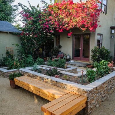 This is an example of a mid-sized traditional partial sun backyard gravel landscaping in Los Angeles for spring.
