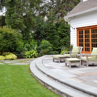 Inspiration for a large traditional full sun backyard stone landscaping in Boston.