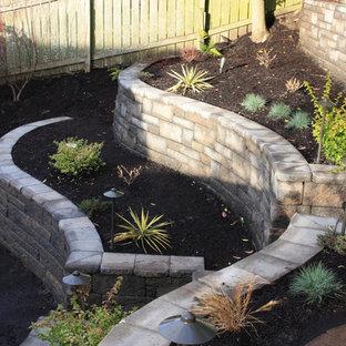 Foto de jardín de secano, clásico, de tamaño medio, en verano, en patio trasero, con muro de contención, exposición parcial al sol y adoquines de hormigón