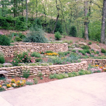 Curved stone retaining walls and huge boulders on hill