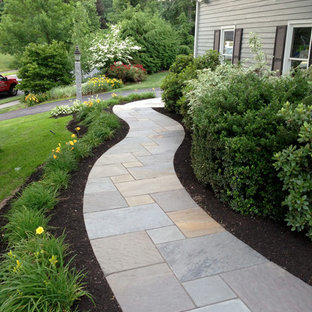 This is an example of a medium sized classic front driveway partial sun garden for spring in Boston with a garden path and concrete paving.