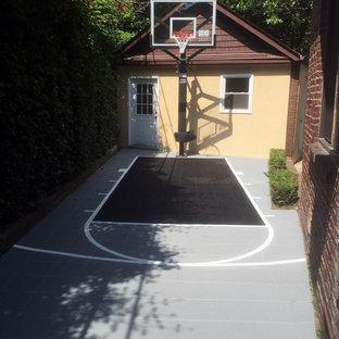 Imagen de pista deportiva descubierta moderna, pequeña, en patio trasero, con parque infantil y exposición parcial al sol