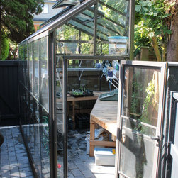 Custom Greenhouses - This greenhouse is an optical illusion.  It is actually a triangle.  Our customer had a small, corner area in her yard up against a fence that we worked with to design the greenhouse.  She is thrilled with the end product!