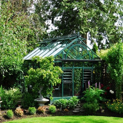 Custom Greenhouses - The Providence greenhouse offers the beauty of a conservatory with the budget of a greenhouse.  Our standard hobby greenhouse frame is upgraded with decorative pressure cap, gutter, beautiful ridge cresting and wagon wheel design and is 1/5th the budget of a traditional conservatory!