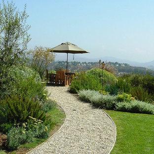 Exemple d'un jardin arrière méditerranéen avec du gravier et des bordures.