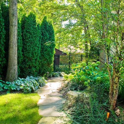Photo of a traditional shade backyard stone landscaping in Chicago.