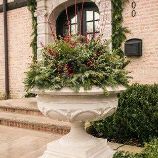 Aménagement d'un grand jardin en pots avant classique l'hiver avec une exposition ensoleillée et des pavés en pierre naturelle.