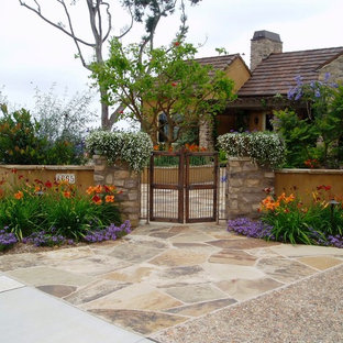 Photo of a mediterranean front yard full sun driveway in San Diego with natural stone pavers and with flowerbed.
