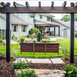 Aménagement d'un grand jardin arrière montagne avec un paillis et une exposition ensoleillée.