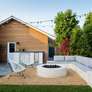 Inspiration for a mid-century modern backyard gravel landscaping in Orange County with a fire pit.