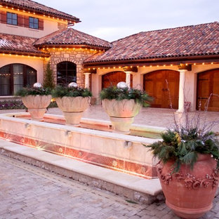 Design ideas for a mediterranean full sun front yard stone driveway in Kansas City for winter.