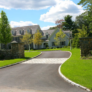 This is an example of a large traditional partial sun front yard stone landscaping in Boston.