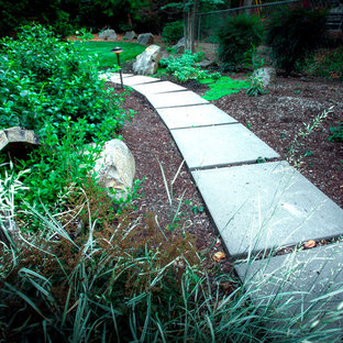 This is an example of a mid-sized mid-century modern partial sun side yard concrete paver garden path in Portland for fall.