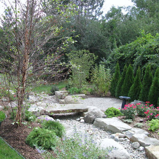 Design ideas for a small rustic back xeriscape full sun garden for summer in Detroit with natural stone paving and a retaining wall.