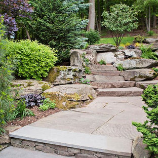 This is an example of a traditional sloped garden in New York with natural stone pavers.