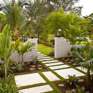 Exotisk inredning av en mellanstor trädgård i full sol framför huset, med en trädgårdsgång och marksten i betong