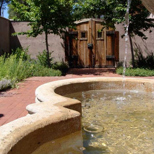 This is an example of a mid-sized traditional partial sun courtyard brick water fountain landscape in Other.