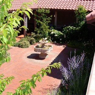 Design ideas for a mid-sized traditional partial sun courtyard brick water fountain landscape in Other.