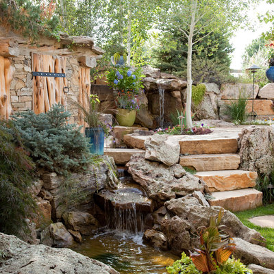 Design ideas for a large traditional partial sun backyard stone landscaping in Denver.