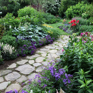 Photo of a large traditional partial sun backyard brick landscaping in New York.