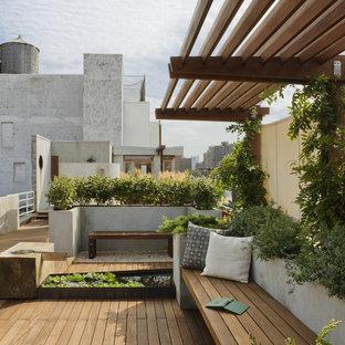 Klassisk inredning av en stor takterrass i full sol, med en fontän och trädäck
