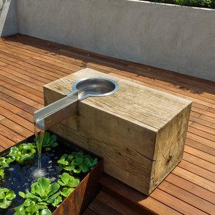 Esempio di un grande giardino moderno esposto in pieno sole sul tetto con fontane e pedane