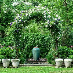 Diseño de jardín tradicional, de tamaño medio, en primavera, en patio trasero, con fuente, exposición parcial al sol y adoquines de piedra natural