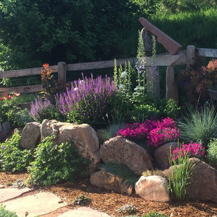 Design ideas for a large eclectic backyard full sun xeriscape in Denver with natural stone pavers and with rock feature.