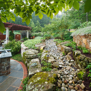 Photo of a mid-sized traditional backyard stone landscaping in DC Metro.