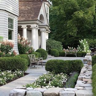 Modelo de jardín francés y parterre de flores, clásico, de tamaño medio, en verano, en patio delantero, con adoquines de piedra natural y exposición total al sol