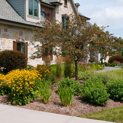 This is an example of a mid-sized traditional full sun front yard concrete paver landscaping in Milwaukee for summer.